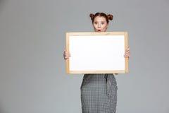 Jeune femme étonnée amusante tenant le tableau blanc vide Photographie stock
