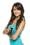 Jeune femme étonnée avec le distant de TV Photographie stock