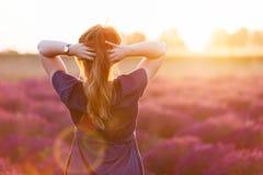 Jeune femme touchant ses longs cheveux sombres regardant le gisement de lavande le coucher du soleil images stock