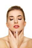Jeune femme touchant son cou Photo stock
