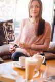 Jeune femme traînant avec son furet d'animal familier en café Image libre de droits