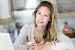 Jeune femme travaillant à l'ordinateur portable et au café potable image stock