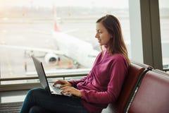 Jeune femme travaillant à l'ordinateur portable et au vol de attente Images stock