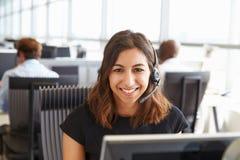 Jeune femme travaillant à un centre d'appel, regardant à l'appareil-photo photographie stock libre de droits