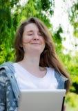 Jeune femme travaillant à une tablette en stationnement photographie stock