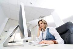 Jeune femme travaillant au bureau Photographie stock libre de droits