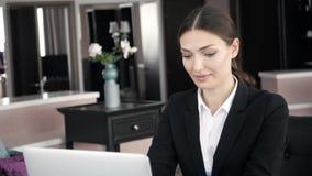 Jeune femme travaillant au bureau moderne avec un ordinateur portable, occupé avec l'enseignement à distance, dans la chambre d'h banque de vidéos