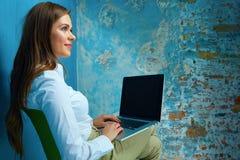 Jeune femme travaillant avec l'ordinateur portable dans la chambre moderne Image stock