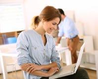Jeune femme travaillant avec l'ordinateur portable sur des jambes images libres de droits