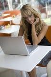 Jeune femme travaillant avec un ordinateur portatif dans un café Photo libre de droits