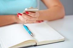 Jeune femme travaillant avec un téléphone portable Image stock