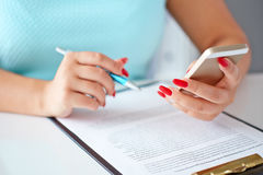 Jeune femme travaillant avec un téléphone portable et tenant un stylo Photo stock
