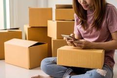 Jeune femme travaillant des affaires en ligne à l'aide du téléphone intelligent Photo stock