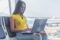 Jeune femme travaillant sur l'ordinateur portable se reposant dans un salon de départ d'aéroport Photos libres de droits