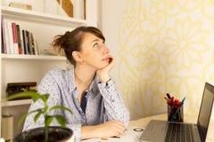 Jeune femme travaillant sur son ordinateur portable à la maison regardant à un côté dans t Images libres de droits