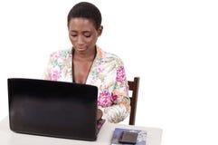 Jeune femme travaillant sur un ordinateur portable au bureau photo stock