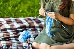 Jeune femme tricotant Oudoors en parc Photo libre de droits