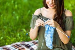 Jeune femme tricotant Oudoors en parc Images stock