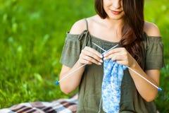 Jeune femme tricotant Oudoors en parc Images libres de droits