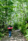 Jeune femme trimardant avec le sac à dos dans la forêt Image stock