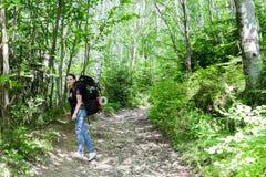 Jeune femme trimardant avec le sac à dos dans la forêt Photo libre de droits