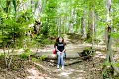 Jeune femme trimardant avec le sac à dos dans la forêt Photos stock