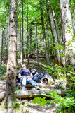 Jeune femme trimardant avec le sac à dos dans la forêt Images libres de droits