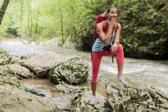 Jeune femme trimardant dans la forêt image stock