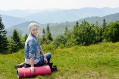 Jeune femme trimardante s'asseyant sur la montagne avec la vallée sur le fond Photographie stock libre de droits