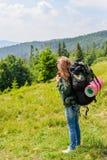 Jeune femme trimardante se tenant sur la montagne avec la vallée sur le fond Photo libre de droits