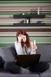 Jeune femme triste avec la carte de crédit et l'ordinateur portable Photo libre de droits
