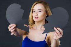 Jeune femme triste couverte par le coeur brisé Images stock
