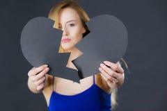 Jeune femme triste couverte par le coeur brisé Image stock