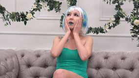 Jeune femme triste dans la perruque avec le mal de tête massant ses temples avec le concept de mouvement circulaire, de soins de  Image stock