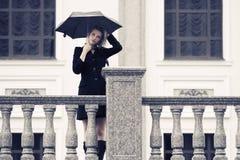Jeune femme triste de mode avec le parapluie marchant dans la rue de ville Photos stock