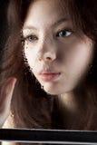 Jeune femme triste derrière l'hublot humide Photographie stock libre de droits