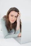 Jeune femme triste occasionnelle décontractée à l'aide de l'ordinateur portable dans le lit Photos stock