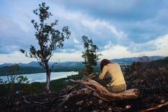 Jeune femme triste s'asseyant sur la colline brûlée Image stock