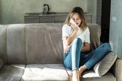 Jeune femme triste s'asseyant sur le divan ? la maison et pleurer photos stock
