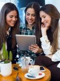 Jeune femme trois à l'aide du comprimé numérique à la boutique de café Photographie stock