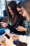 Jeune femme trois à l'aide du téléphone portable à la boutique de café Images stock