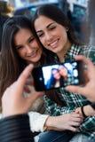 Jeune femme trois à l'aide du téléphone portable à la boutique de café Photos stock