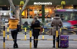 Jeune femme trois à un arrêt d'autobus Photographie stock