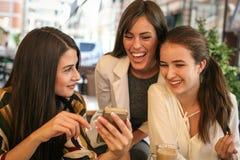 Jeune femme trois s'asseyant en café utilisant le téléphone intelligent Photo libre de droits