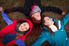 Jeune femme trois se trouvant sur une herbe d'automne Photos stock