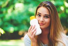 Jeune femme une bouteille de sunblock dehors images libres de droits