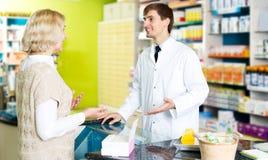 Jeune femme utile de portion de pharmacien dans la pharmacie images libres de droits
