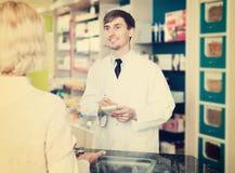 Jeune femme utile de portion de pharmacien dans la pharmacie image libre de droits