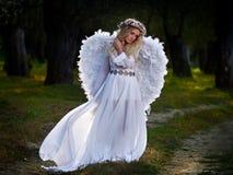 Jeune femme utilisant de longues ailes blanches de robe et d'ange photos stock