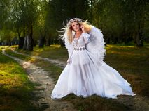 Jeune femme utilisant de longues ailes blanches de robe et d'ange photographie stock libre de droits